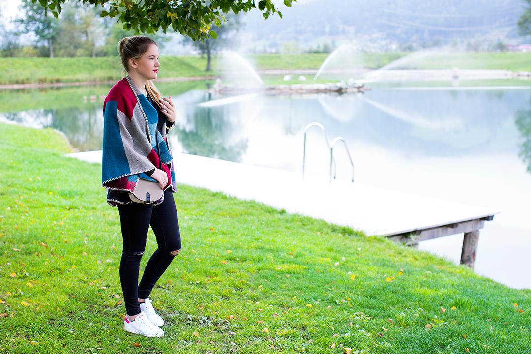 Whynot Outfitshooting auf einem Steg im See mit Cape und schwarzer Hose und Stan Smith Adidas Schuhe