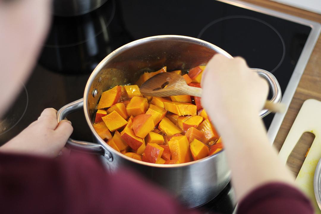 Umrühren während die Kürbisstücke kochen.