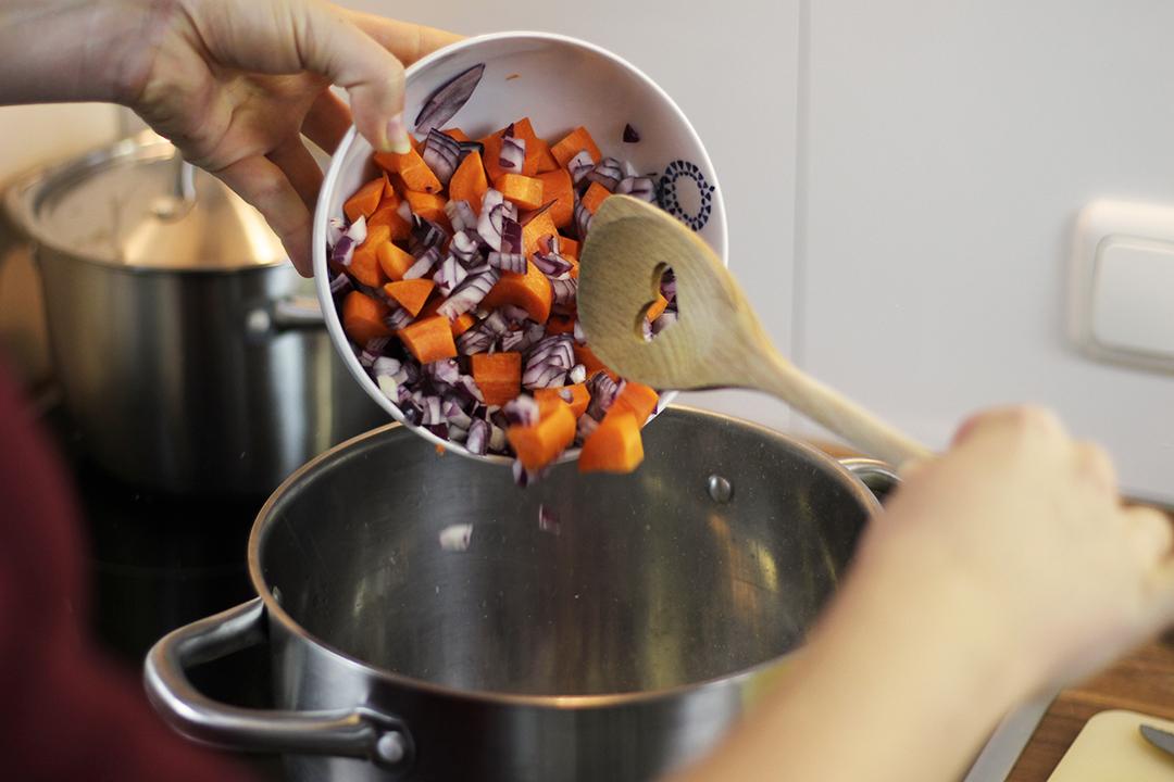 Kürbis und Zwiebelstücke kommen in den Kochtopf.