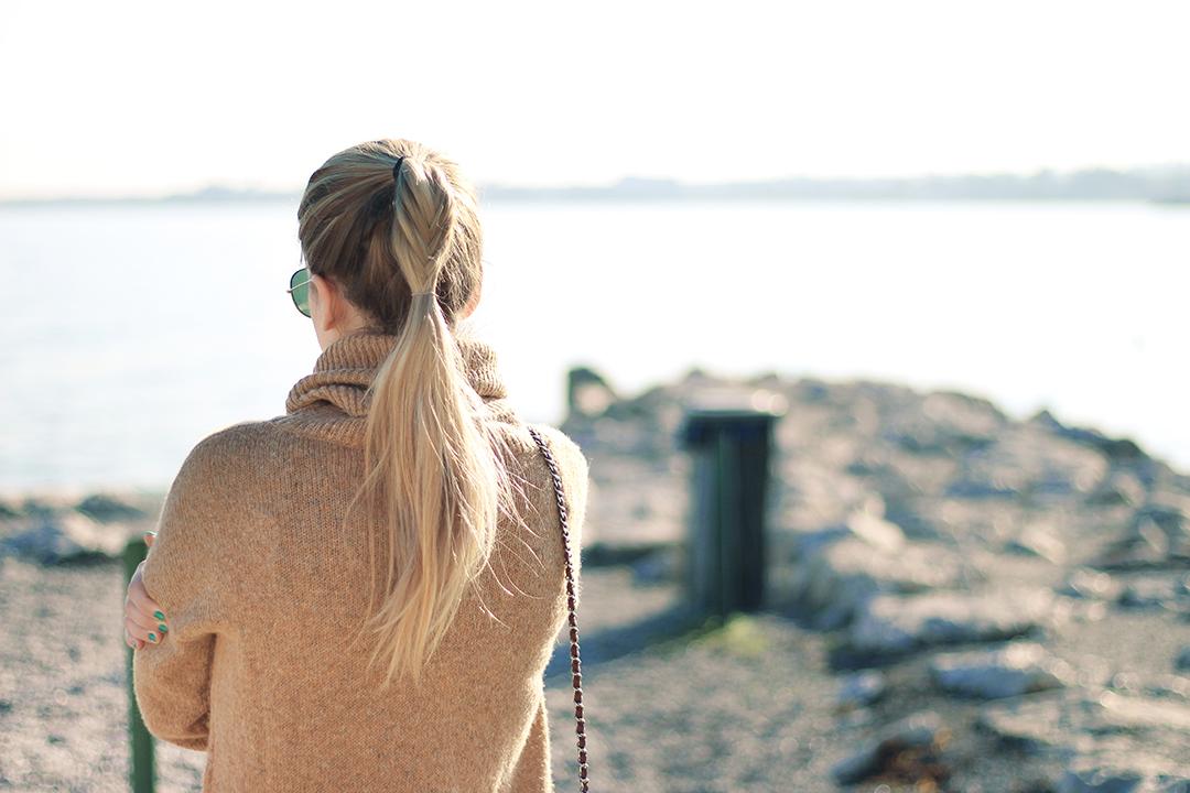 Am Gardasee mit schwarzer Hose und braunem Pullover von Hinten mit einem Fischgrätenzopf