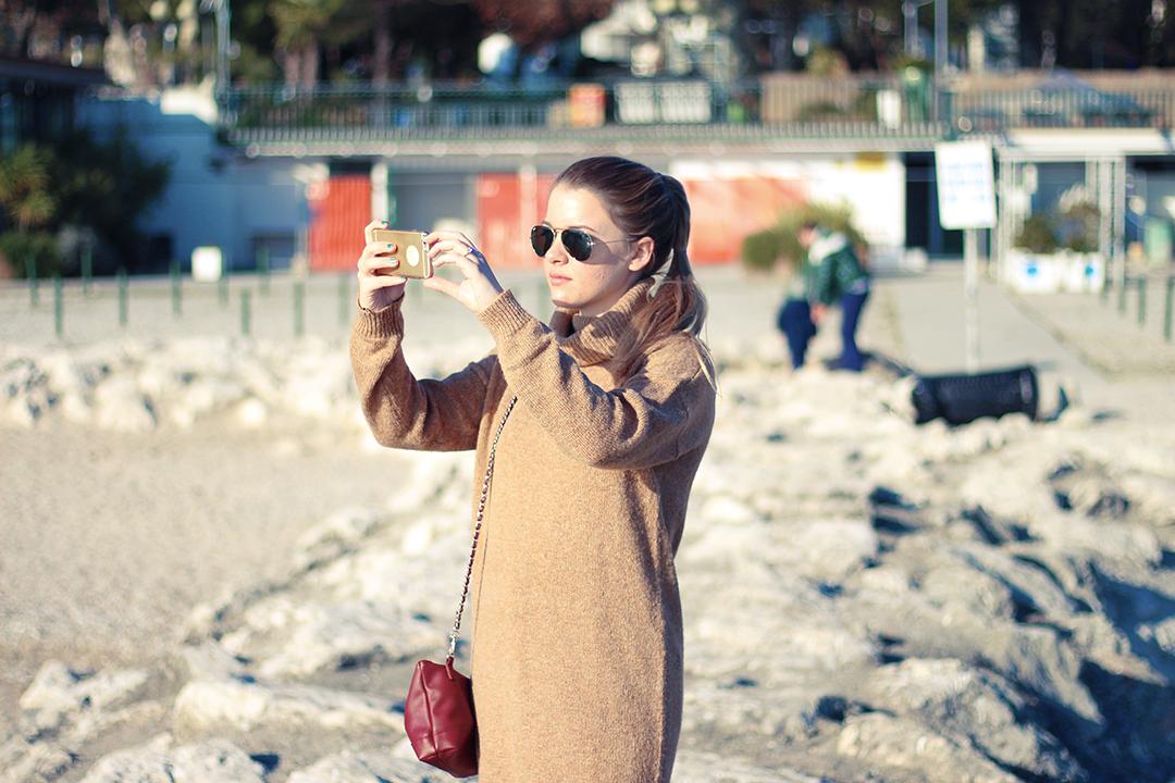 Am Gardasee mit schwarzer Hose und braunem Pullover taking a selfie