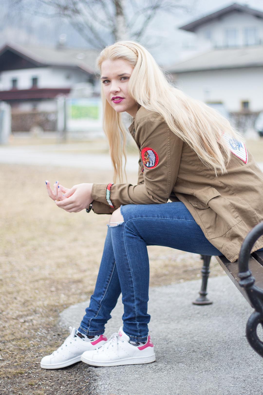 Grüne Patches Jacke mit blauer Jeans und Stand Smith Sneaker