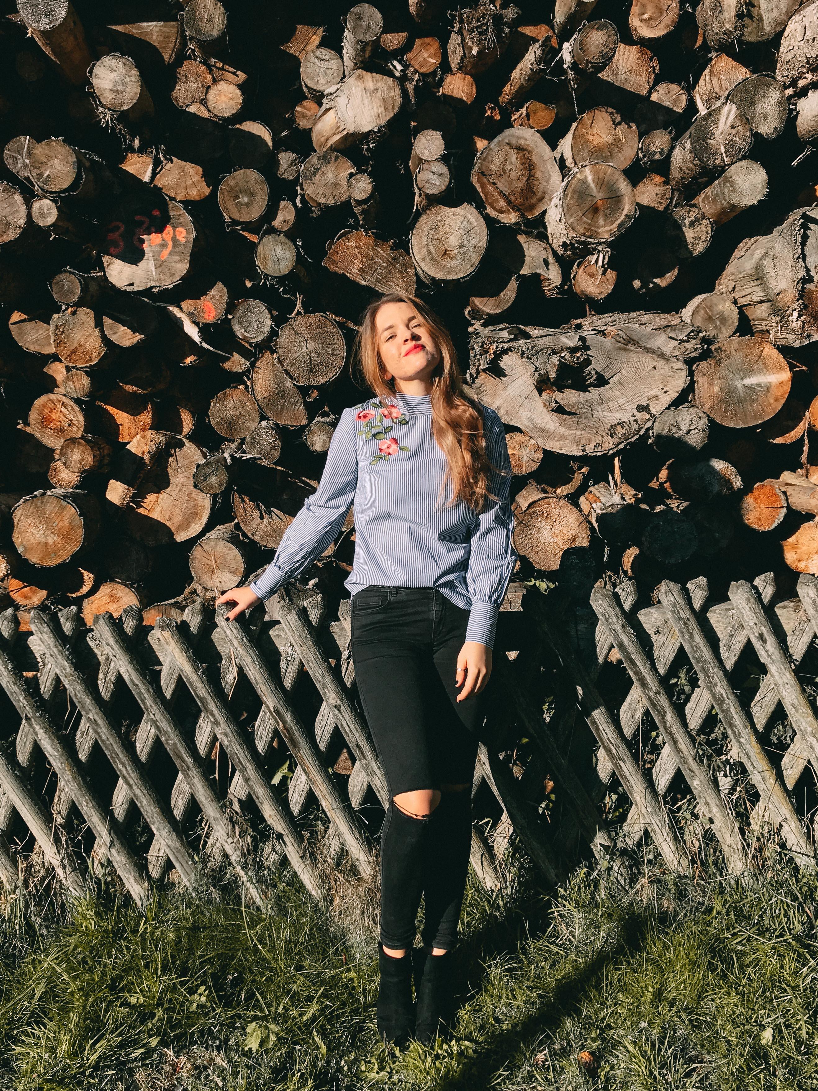 Bild von Saskia vor einem Holzstapel